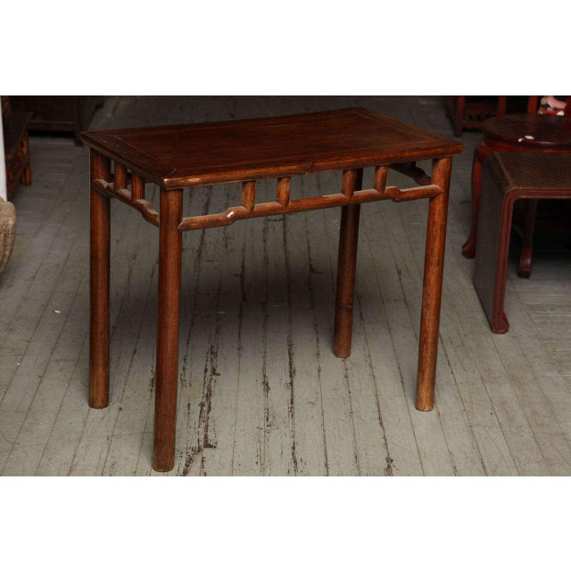 This 19th century Chinese small console or wine table was made with elmwood during the Qing Dynasty (1644-1912). The table...