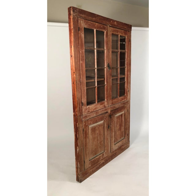 A 19th century American painted country corner cupboard, circa 1840, with wonderful old surface, in pine with layers of...