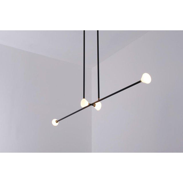Designed by Taylor McKenzie-Veal and Brendan Keim, opaque glass and brass shades seamlessly blend into a matte black...