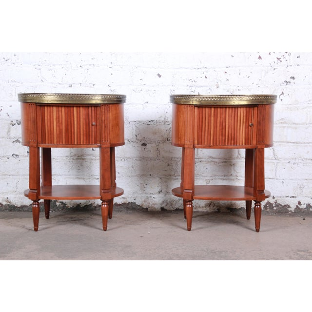 An exceptional pair of French Regency Louis XVI nightstands or end tables by Baker Furniture. The nightstands feature...