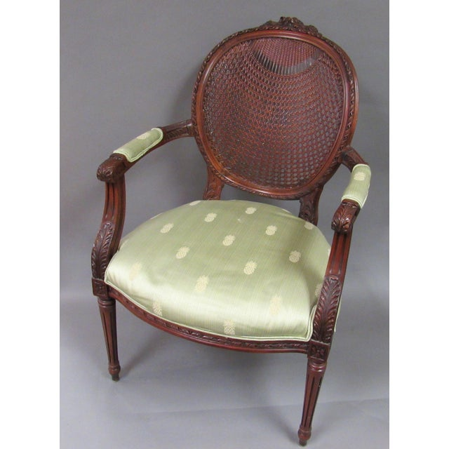 Fantastic late 20th c., Louis XVI style fauteuil having a floral crest over an oval back with intricate woven cane work....