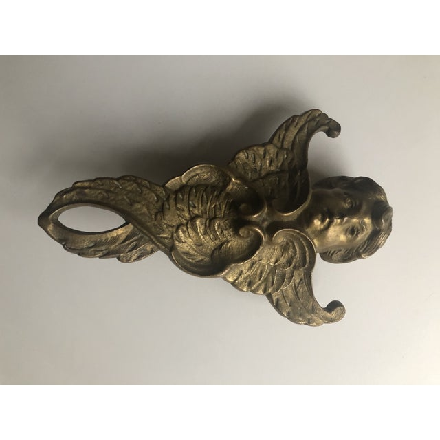 A beautiful and substantial heavy piece of brass. What looks like a door stop is in the form of an angel or cherub. An...