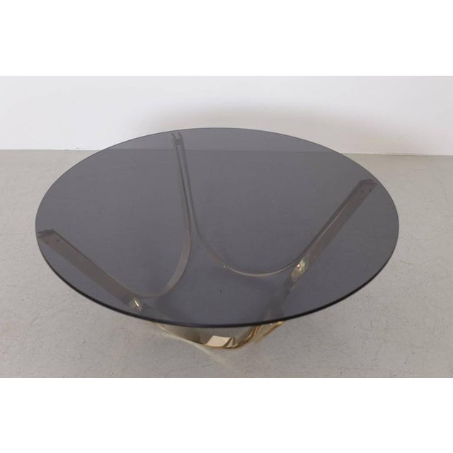 Coffee table in the style of Roger Sprunger for Dunbar. The thick smoked glass top has no chips and the base is in...
