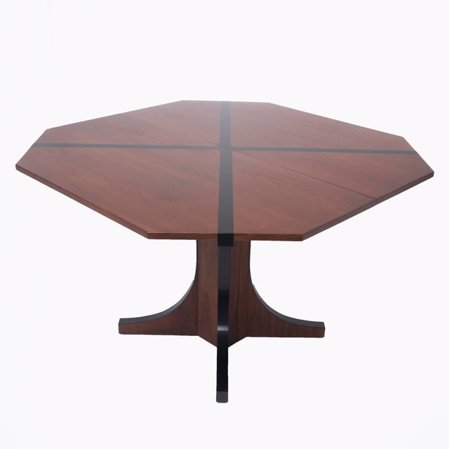 A dining table designed by John Kapel for Glenn of California with a truncated square top inlaid with a black laminate...