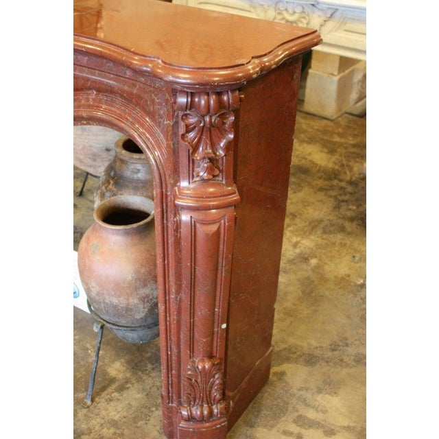 Exquisite hand-carved mid-19th century red marble mantel tastefully done in Louis XV style. One of over 130 mantels in stock!