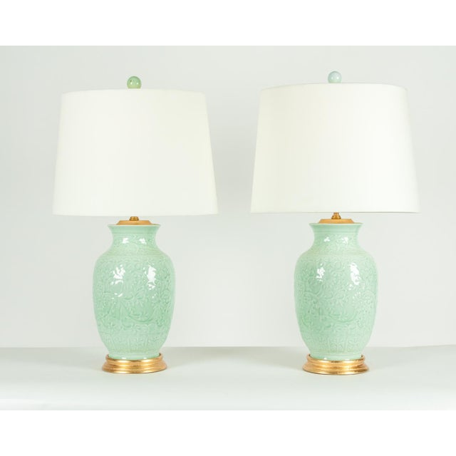 Midcentury porcelain pair of table lamps with wood gold leaf base. Each lamp is in excellent working condition. Each lamps...