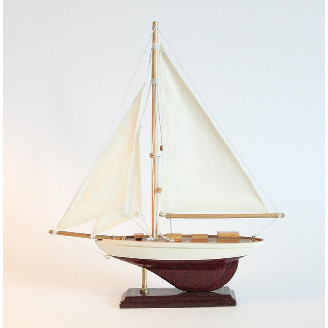 A wonderful model sail boat. Cloth sails. Carved, painted and stained. Mounted on a stand for display. Great for your...