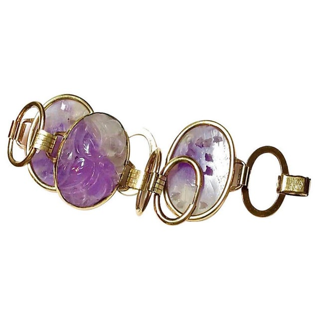 Circa 1950s gold-filled, large link bracelet that is bezel set with three oval floral carved amethysts. The bracelet...