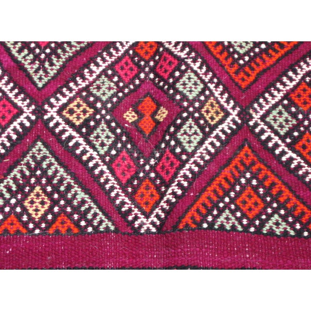 Elaborate Moroccan Vintage Kilim Rug in lush magenta wool with vibrantly colored embroidery and a diamond design on edges.