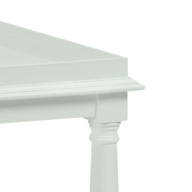 Made of acacia wood, this cocktail table features a gallery shelf and turned legs. Color is Benjamin Moore Gray Cashmere...