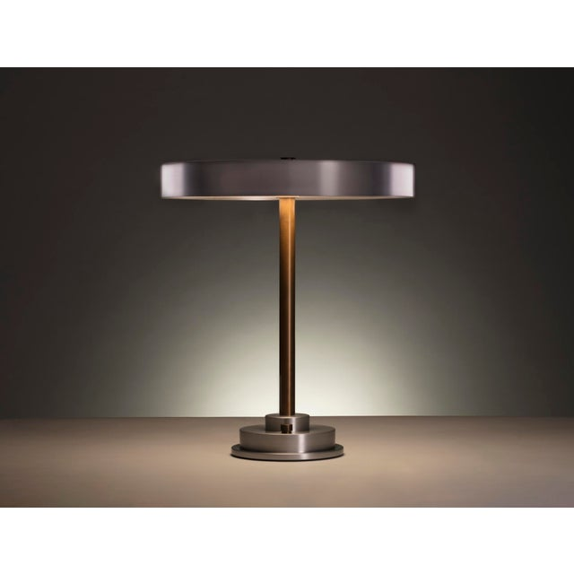 The shade of the Disc Lamp can either fade into its surroundings or catch light to emphasize its refined form. The...
