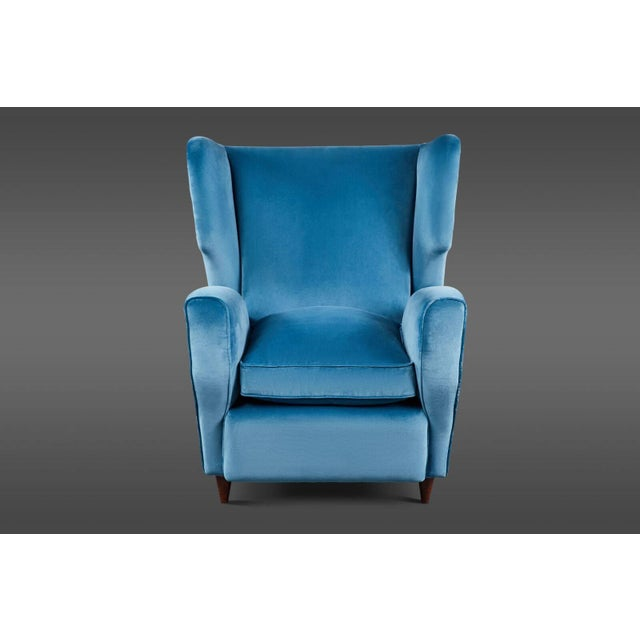 A curvaceous pair of Italian mid-20th century wingback armchairs in two tones of blue velvet with loose, overstuffed down...