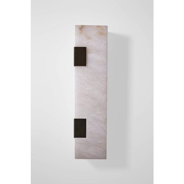 This contemporary light made of blackened brass and alabaster is part of the Orphan Work brand and can be used as a wall...