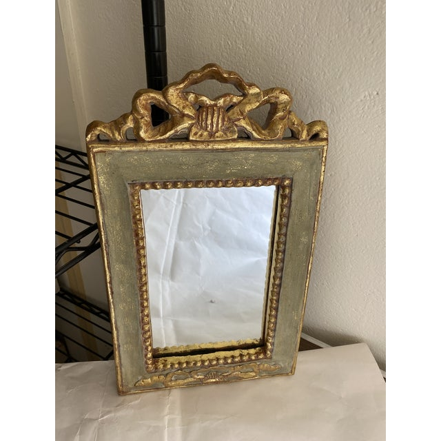 Small neoclassical style mirror painted in pale green with gold highlights