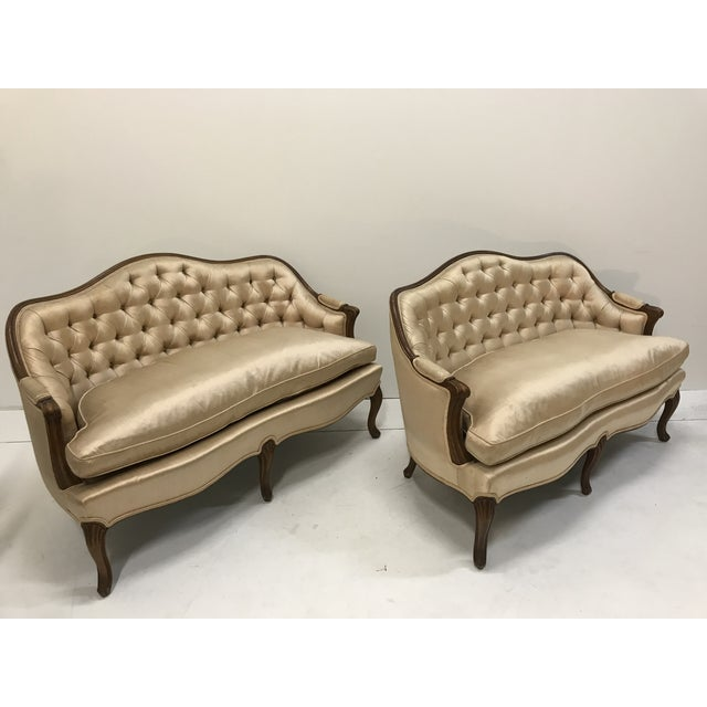 Matching pair of tufted loveseats in a Champaign color satin fabric with few spots but no holes snags or tears to the...