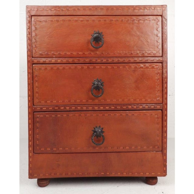 Handsome Mid-Century three-drawer chest or nightstand features Spanish cordovan leather and unique metal pulls. The...