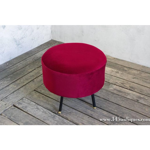 Small red chenille footstool/ottoman on metal legs.