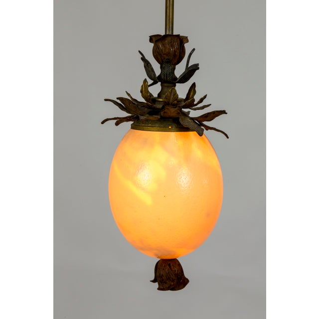 Gorgeous, hand crafted pendant light made with an ostrich egg and antique metal, floral decorative elements on a brass...