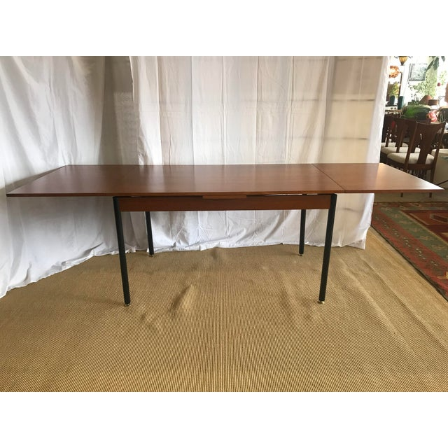 Refinished extendable- leaf teak dining table with black metal pipe design legs and adjustable brass feet. By ISA Bergamo,...