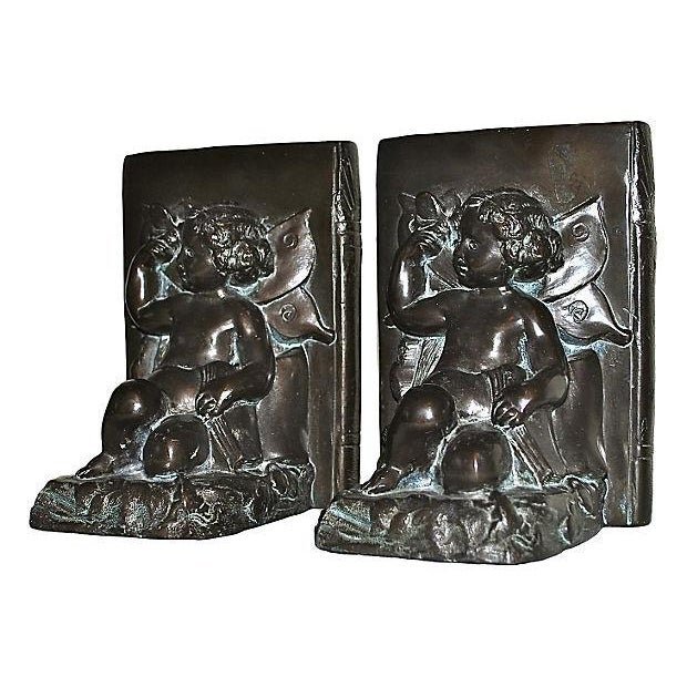 A lovely pair of bookends featuring cherubs with butterflies and books, each leaning on a vertical book with remnants of...