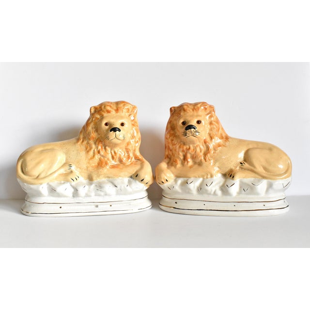 A pair of large, Vintage Staffordshire-style lion mantel figurines with glass eyes, reclining on white bases with gilt...