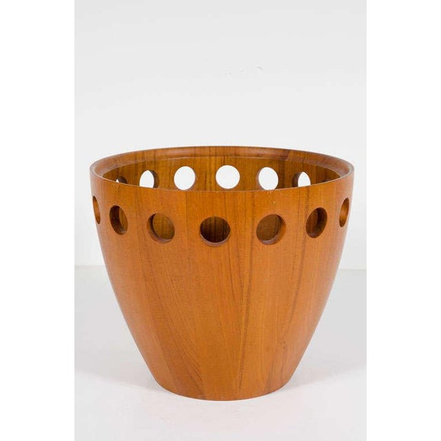 A Danish modern fruit bowl made in strips of staved teak with circles pierced around the top and an interior carved rim....