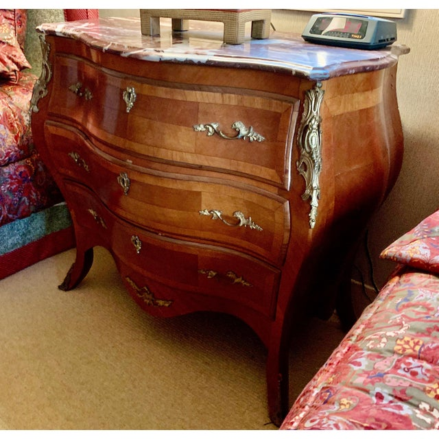 Full bombe curves swell onto the sides as well. Finely veneered wood throughout, with contrast banding on the drawers,...
