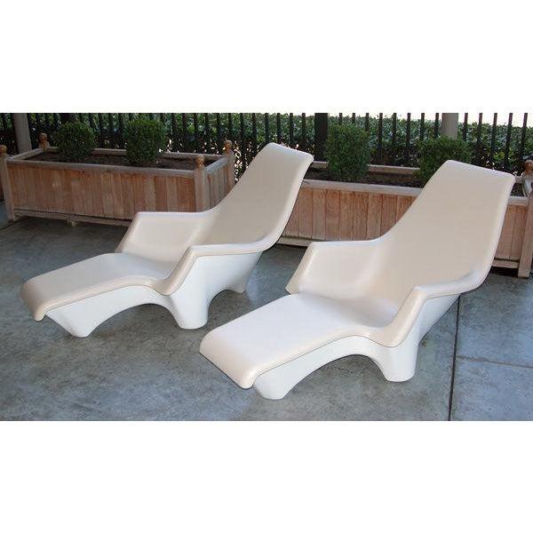 A stylish and sculpted pair of American 1960's fiberglass outdoor lounge chairs; each with flowing scrolled back above a...