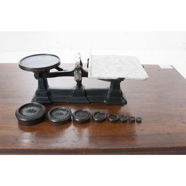 English cast iron scale with a white marble weighing platform. This scale has eight original weights: 4lb, 2lb, 1lb, 8oz,...