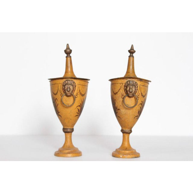 A pair of Regency tole painted chestnut urns with lids. Each tapering form is decorated with images of figures with...