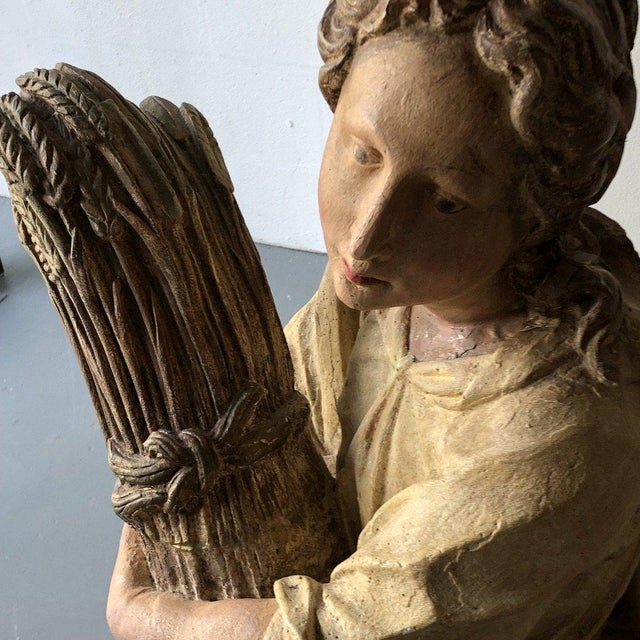 Figure holding a wheatsheaf labeled Montecello Studios. Height: 46″ Width: 17.5″ Depth: 15.5″