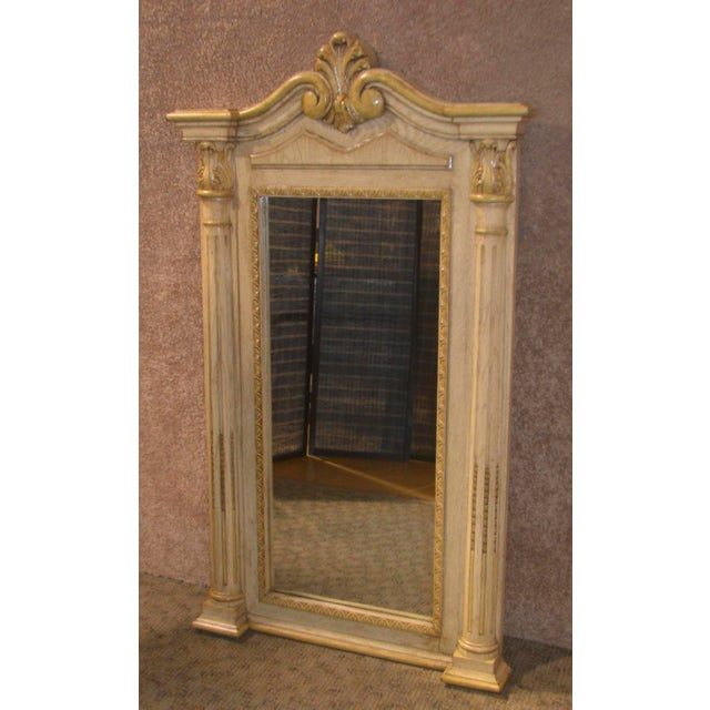 Wall Mirror has an Italian Style with column detail. The frame color is Antiqued Antique White. The frame material is wood...
