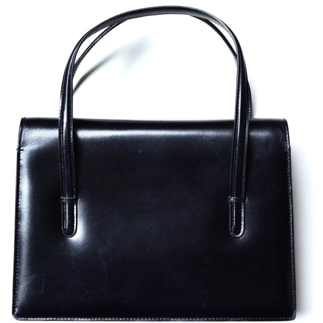 Signed Gucci soft, but structured black 1960s handbag. The bag is clean inside. Lovely classic design. Opens with a snap...
