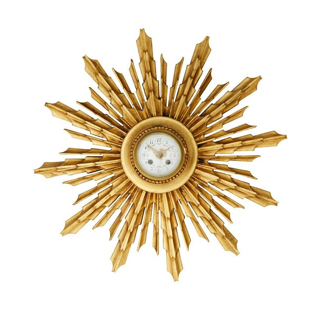 A gilded wall clock in the form of radiant rays. Hand carved in wood and made in the 1900's. Enamel dial and modern...