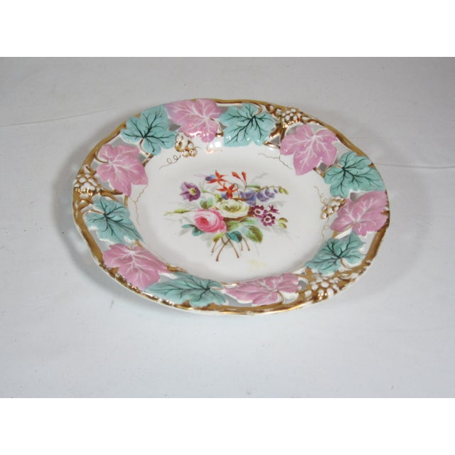 The bowl has a open work boarder with leaves in alternating colors of mauve and turquoise, the center has a multi colored...