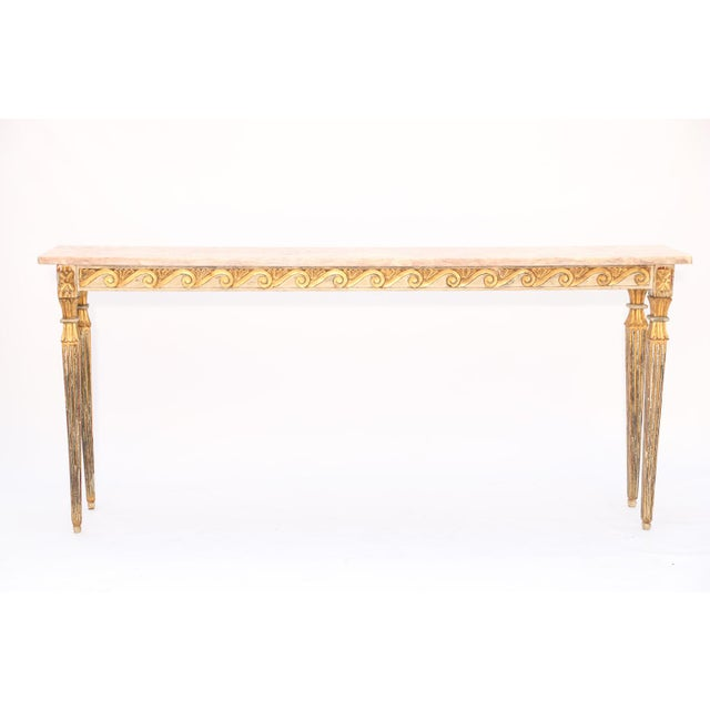 Console table, having a long and narrow form, its rectangular top of rouge marble, set on a painted and parcel-gilt table...