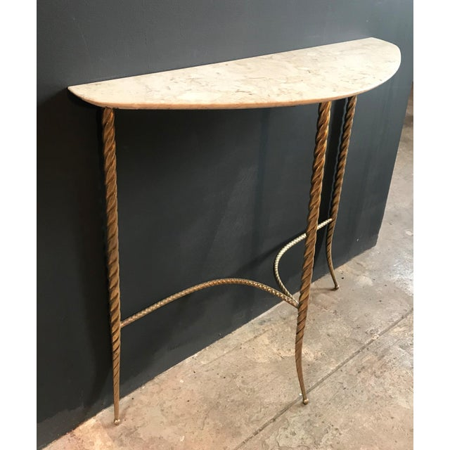 This elegant and tiny console table stands on three legs in full brass and a shaped cream marble top. Italy, 1940s.