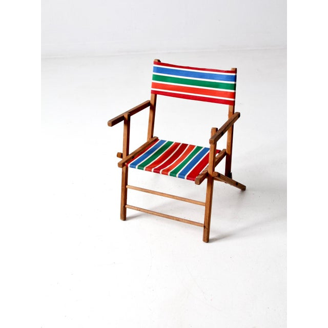 This is a mid-century children's folding chair. The wooden frame chair features a vibrant striped cotton seat and back in...