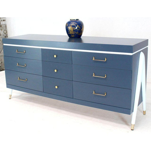 Mid-Century Modern long credenza nine drawers dresser with exposed sculptural compass shape legs. Brass hardware pulls.