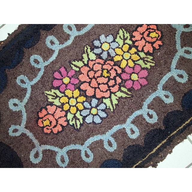 Handmade antique oval American hooked rug in good condition. Deep chocolate brown background decorated with a large...