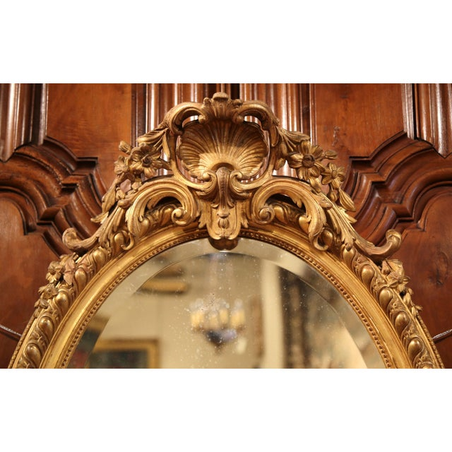 This elegant, antique wall mirror was created in France, circa 1870. The feminine, oval mirror features a decorative shell...