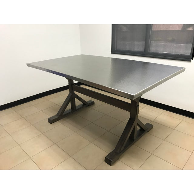 "Amazing gathering table! Stainless steel top. Mindi Solids. Trestle-styled in portobello finish. Top: 72"" w x 42"" d x 1.5..."