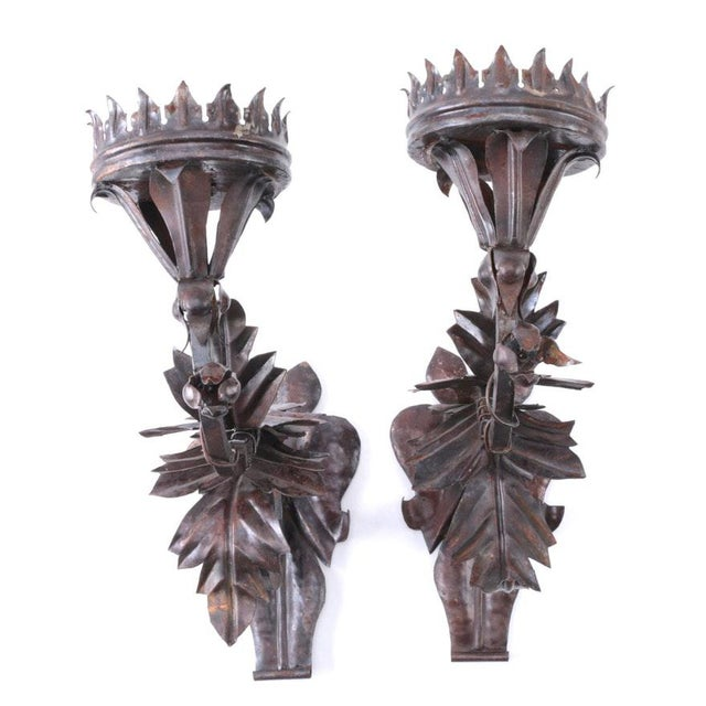 A pair of metal floral motif decorative wall mounted candle sconces. These two sconces have an elaborate floral and leaf...