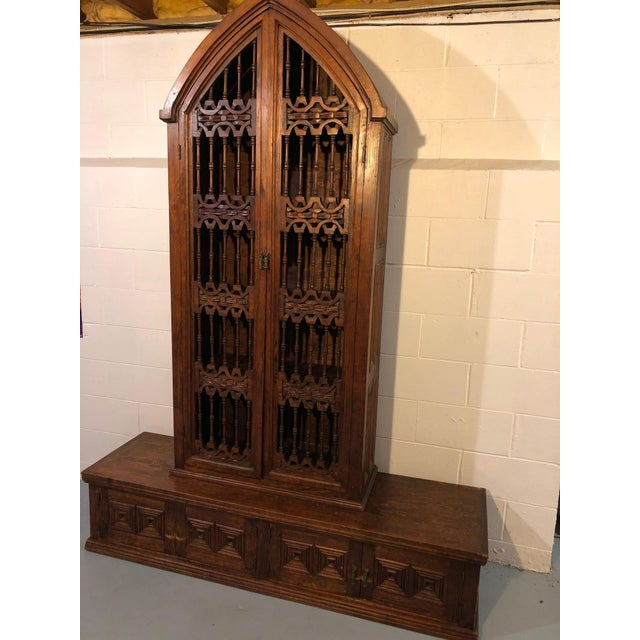 A one of a kind hand crafted ornately carved mahogany bookcase from New Orleans having tall church like arched Gothic...