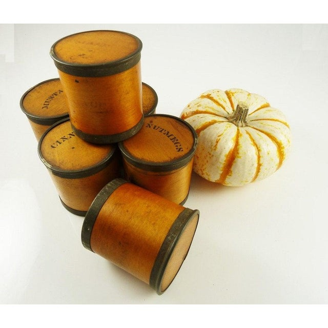 A set of six antique Bentwood spice boxes manufactured by the Patent Package Co. The boxes have a warm mellow look with...