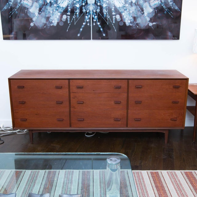 Clean nine-drawer triple dresser in teak with unique angled solid teak drawer pulls that closely resemble those of Poul...
