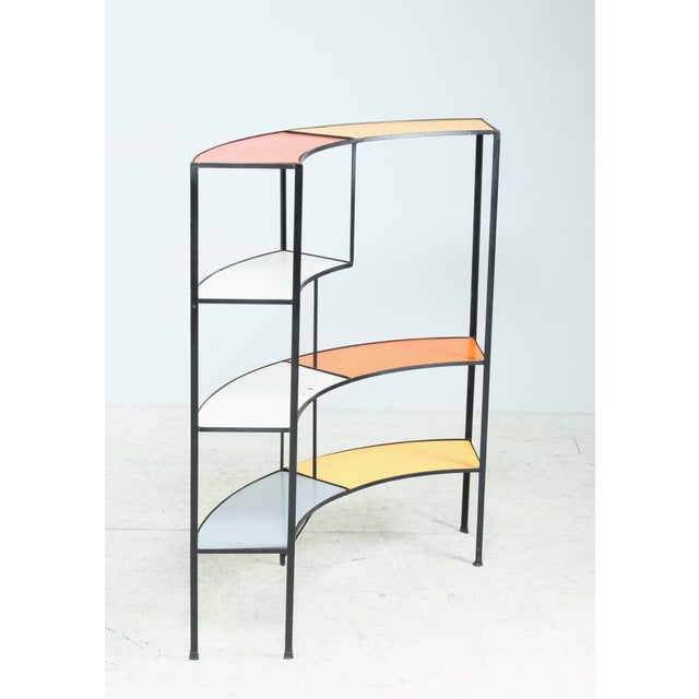 A colorful shelving unit by American designer Frederic Weinberg. This unit is made of a wrought iron frame with coated...