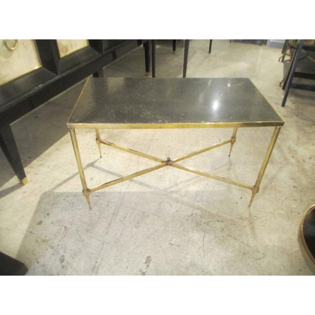 Bagues brass coffee table with marble top in the neoclassic manner with stretcher base on reeded legs.