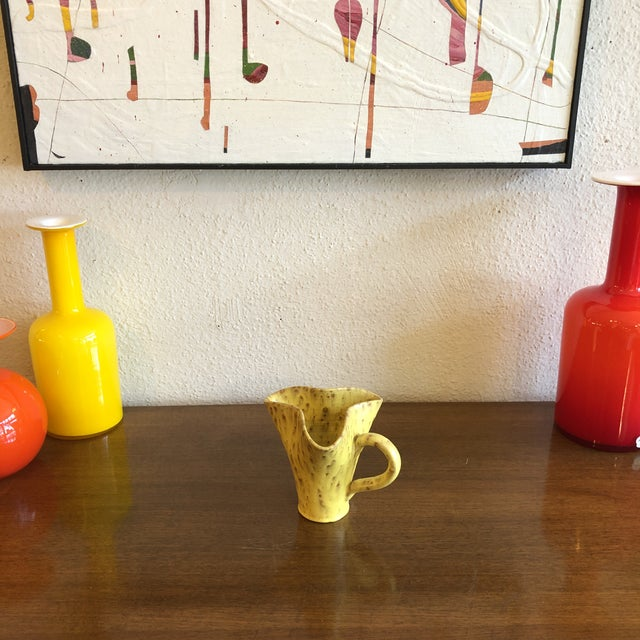This quaint handled pinched pitcher by Jerk Werkmaster, creative director at Sweden's Nittsjö Keramik from 1933-1967,...