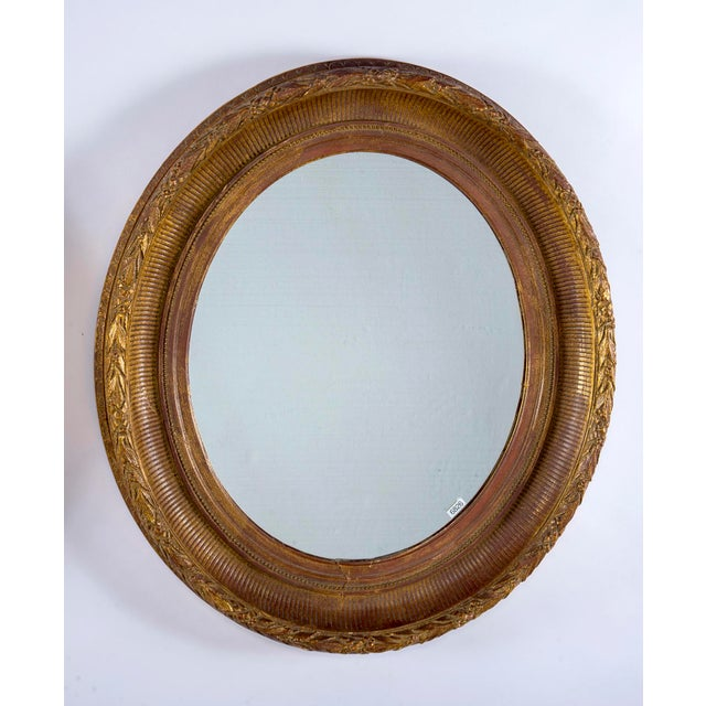 Circa 1880 near pair oval mirrors with wide carved gilt wood and gesso frames. Frames are not perfectly symmetrical but...